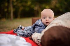 Gulliga små behandla som ett barn pojken som ligger på en filt i parkera royaltyfri fotografi