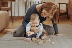 Gulliga små behandla som ett barn pojken som spelar med träkvarter Royaltyfria Foton