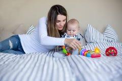 Gulliga små behandla som ett barn pojken som spelar med hans mamma som är hemmastadd i säng med l Royaltyfria Foton