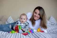 Gulliga små behandla som ett barn pojken som spelar med hans mamma som är hemmastadd i säng med l Royaltyfri Foto