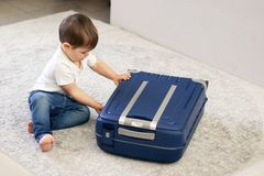 Gulliga små behandla som ett barn pojken som stänger den blåa resväskan, avslutade sig inpackning för semester royaltyfri bild