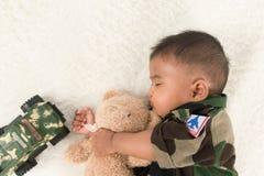 Gulliga små behandla som ett barn soldaten, i att sova för likformig arkivbild