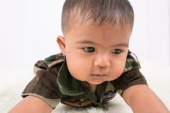 Gulliga små behandla som ett barn soldaten i likformign som ligger på den mjuka filten royaltyfri fotografi