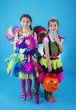 Gulliga små flickor i allhelgonaaftondräkter som är klara att gå trick eller behandling fotografering för bildbyråer