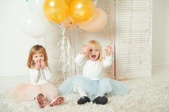 Gulliga små flickor i klänningar som tillsammans spelar i ljust rum Lyckligt födelsedagbegrepp royaltyfri fotografi