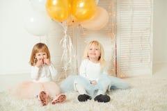 Gulliga små flickor i klänningar som tillsammans spelar i ljust rum Lyckligt födelsedagbegrepp royaltyfria foton