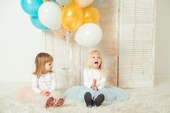 Gulliga små flickor i klänningar som tillsammans spelar i ljust rum Lyckligt födelsedagbegrepp royaltyfria bilder