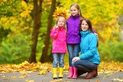 Gulliga små flickor och deras moder som har gyckel på härlig höstdag Lyckliga barn som spelar i höst, parkerar Ungar som samlar y Royaltyfri Fotografi