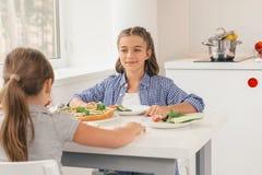 Gulliga små flickor som äter sund mat i kök Arkivfoton
