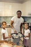 Gulliga små flickor som sammanfogar deras fader, medan sätta kakor in till ugnen arkivbild