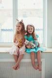 Gulliga små flickor som sitter vid fönstret Royaltyfri Foto