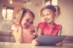 Gulliga små flickor som spelar på digital flik Arkivfoton