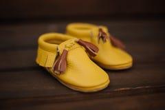 Gulliga små gula barnskor med brunt snör åt Arkivbild