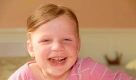 Gulliga små leenden för en flicka En liten flicka med chokladpralinfläckar på framsida En liten flicka sitter i köket Arkivfoto