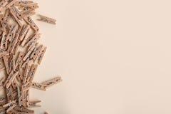 Gulliga små träklädnypor på en kräm- bakgrund royaltyfri bild