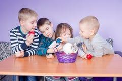 Gulliga små ungar som spelar med målade ägg Arkivbilder