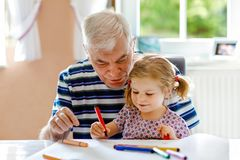 Gulliga sm? behandla som ett barn litet barnflickan och stilig h?g farfarm?lning med hemmastadda f?rgrika blyertspennor Barnbarn  arkivbild