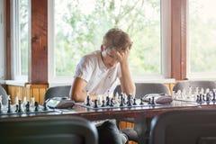 Gulliga smart, sitter spelar 11 år gammal pojke i den vita skjortan i klassrumet och schack på schackbrädet Utbildning kurs, hobb royaltyfria foton