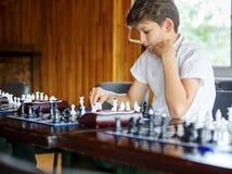 Gulliga smart, sitter spelar 11 år gammal pojke i den vita skjortan i klassrumet och schack på schackbrädet Utbildning kurs, hobb royaltyfri bild