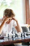 Gulliga smart, sitter spelar 11 år gammal pojke i den vita skjortan i klassrumet och schack på schackbrädet Utbildning kurs, hobb royaltyfria bilder