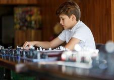 Gulliga smart, sitter spelar 11 år gammal pojke i den vita skjortan i klassrumet och schack på schackbrädet Utbildning kurs, hobb arkivbild