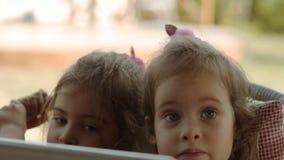 Gulliga systrar rymmer en minnestavla och håller ögonen på en tecknad film på den lager videofilmer