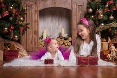 Gulliga systrar som ligger nära julträd arkivbild