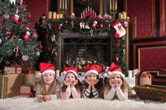 Gulliga systrar som ligger på vit matta nära julträd arkivfoto