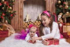 Gulliga systrar som ligger på vit matta nära julträd, bärande rosa färgkjolar och röda huvudbindlar Le små barn white för julgåva Royaltyfria Bilder