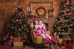 Gulliga systrar som sitter nära julträd Arkivfoto