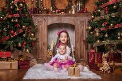 Gulliga systrar som sitter nära julträd Royaltyfri Bild