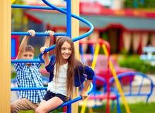 Gulliga tonårs- ungar som har gyckel på lekplats Arkivfoto