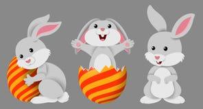 Gulliga tre små kaniner med dekorerade påskägg på en grå bakgrund royaltyfri illustrationer
