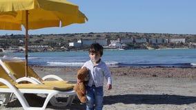 Gulliga två år gammal pojke med den teedy björnen på det mer kalla vädret för sandig strand stock video
