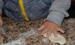 Gulliga två år gammalt spela med pizzadeg arkivbilder