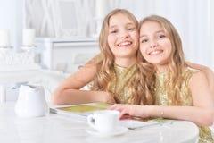 Gulliga tvilling- systrar med den moderna tidskriften Arkivbild