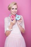 Gulliga unga kvinnor rymmer färgrika donuts soft för fält för färgpildjup grund Arkivbilder