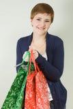 Gulliga unga påsar för shopping för redheadkvinnaholding Arkivfoto