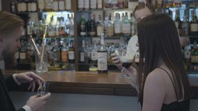 Gulliga unga par som sitter på stången i en dyr restaurang eller en bar Den uppsökte säkra mannen dricker whisky och hans stock video