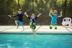 Gulliga unga pojkar som hoppar in i en simbassäng medan på en rolig semester Royaltyfri Foto