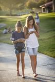 Gulliga unga ton?riga flickor som utomhus smsar p? deras mobila mobiltelefon royaltyfri foto