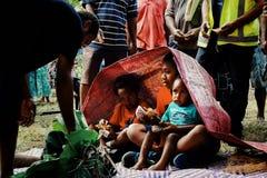 gulliga unga ungar som accepterar offerings som taroen, sötpotatis, traditionella vävde mats för deras omskärelseritual fotografering för bildbyråer