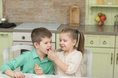 Gulliga ungar bakade kakor och att smaka det på tabellen i det hem- köket royaltyfria bilder