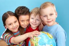 Gulliga ungar med jordklotet Royaltyfri Foto