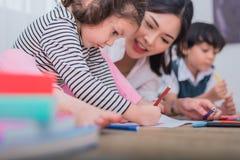 Gulliga ungar och asiatisk lärareteckning i konstnärgrupp Dra tillbaka till skolan och utbildningsbegreppet Barnkammare och f?rsk arkivfoton