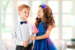 Gulliga ungar, pojke ger en blommaliten flicka valentin för dag s Barnförälskelse Royaltyfri Foto