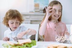 Gulliga ungar som äter deras sunda frukost Arkivfoto