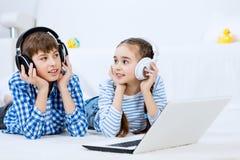 Gulliga ungar som använder apparater Arkivfoton