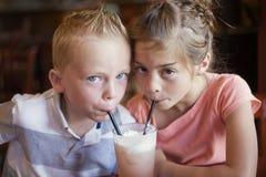 Gulliga ungar som delar en italiensk sodavatten för mintkaramell, dricker på ett kafé arkivbild