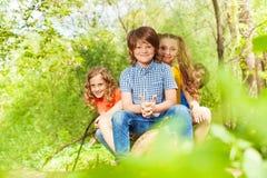 Gulliga ungar som sitter på en inloggning som sommaren parkerar Royaltyfri Bild
